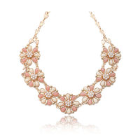 Set in gold tone flower pattern, this pretty choker accents the powder pink and cream resin cabochon beads embedded petals. The special crown motif gold plated link chain is adjustable and securely fastened by a lobster clasp.  Unique and exclusive desi...