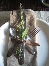 Autumnal leaves or herb sprigs add a natural touch to ribbon-tied cutlery place settings.