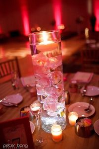 Cymbidium orchids submerged in tall cylinder vases topped with a floating candle