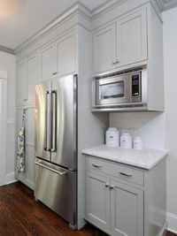Cabinetry, carrara marble countertops, white subway tile backsplash, nickel hardware, stainless steel appliances.