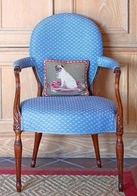A Hepplewhite chair wearing blue linen-and-cotton mini-print boasts a sweet needlepoint puppy pillow - Traditional Home®