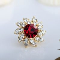 This flower pin features floral pattern encrusted with shinning white and ruby rhinestones.The rhinestone cluster flower brooch is crafted in plated gold over alloy with a butterfly clutch pin.