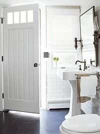 Love the huge dark floor tiles, pedestal sink, hinged mirror and sconces.