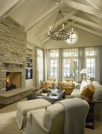 traditional French doors transom windows vaulted ceiling stone fireplace TV jute rug light gray linen slipcover sofa mustard yellow chairs espresso coffee table iron chandelier
