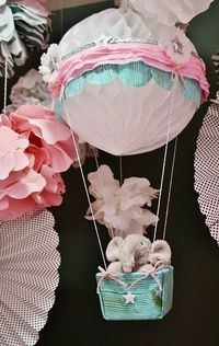 used a Honeycomb Tissue Ball from a large party supply store for the balloon, an empty plastic square container for the basket, along with some fabric, baker's twine, white and pink crepe tissue streamers (also from the party store) ribbon and...